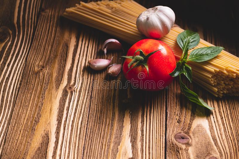 Tasty appetizing italian spaghetti pasta ingredients for kitchen cuisine with tomato, garlic and basil on wooden brown table. Food royalty free stock images