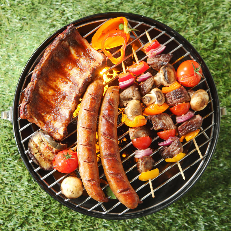 Tasty assortment of meat on a summer barbecue. With sausages, beef kebabs and spare ribs with tomatoes and mushrooms, overhead view over green grass royalty free stock photography