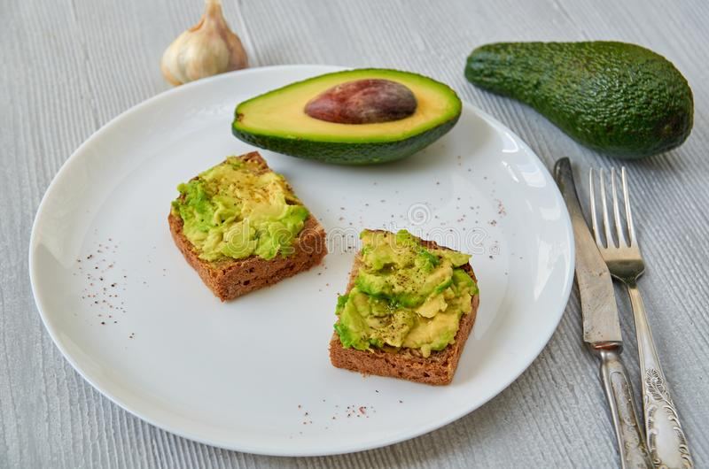 Tasty avocado toasts on the white plate with black salt and garlic. Vegetarian avocado sandwiches on the gray background. With free copy space. General view royalty free stock photography