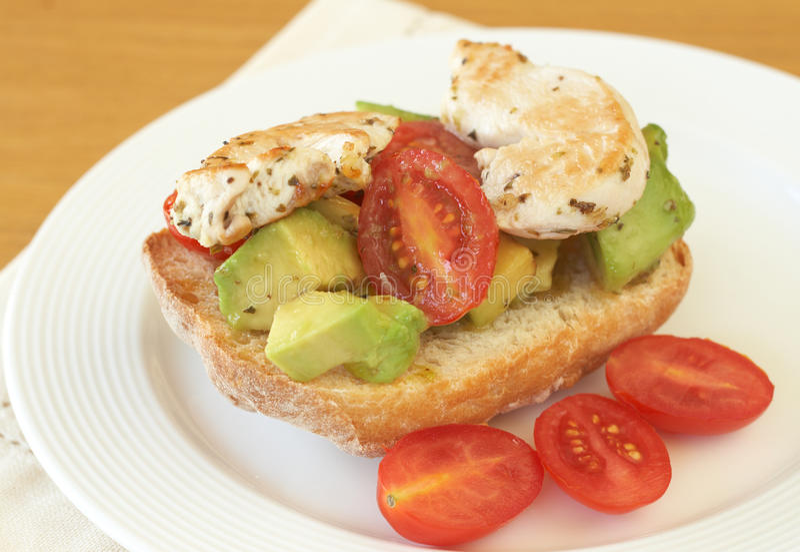 Tasty avocado, tomato and chicken bruschetta royalty free stock photo