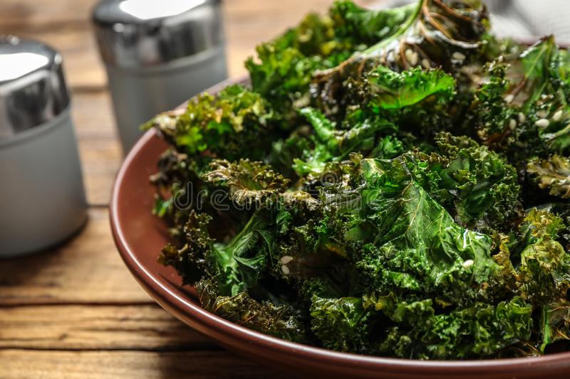 Tasty baked kale chips on wooden table stock photography