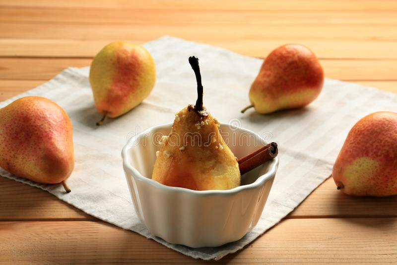 Tasty baked pear in bowl and fresh fruit on wooden table royalty free stock photos