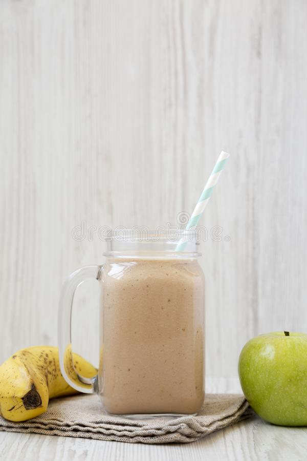 Tasty banana apple smoothie in a glass jar, side view. Closeup royalty free stock photography