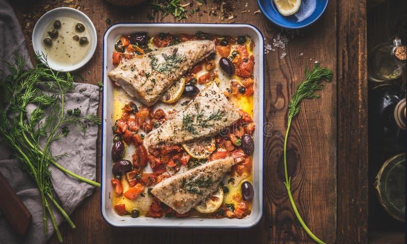 Tasty Bass-visfilets in mediterrane saus met tomaten, olijven en kappen in bakpan op een roestachtige houten achtergrond met royalty-vrije stock fotografie