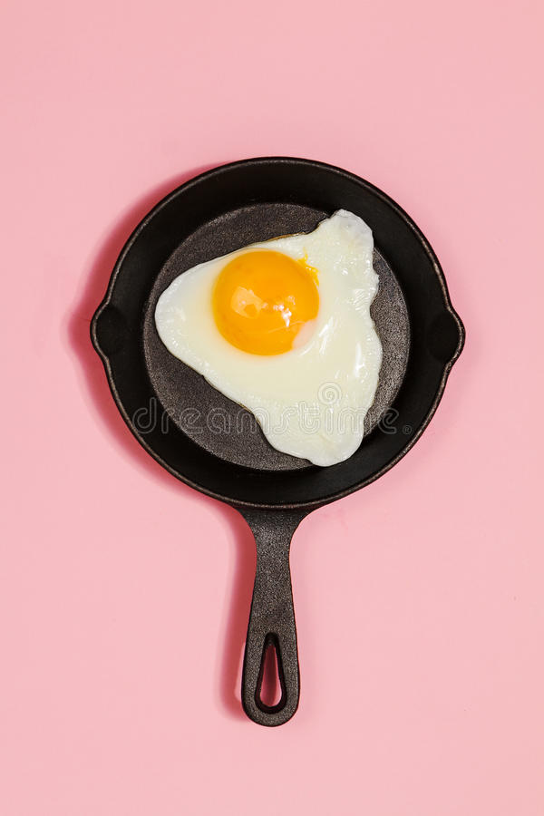 Tasty beautiful food fried egg in pan on fashionable pink background. Minimalistic Concept. Top View. royalty free stock photos