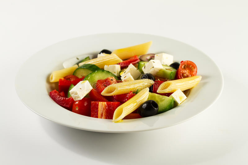 Tasty beautiful greek traditional greek or italian salad with vegetables and pasta on plate. Bright Background. stock images