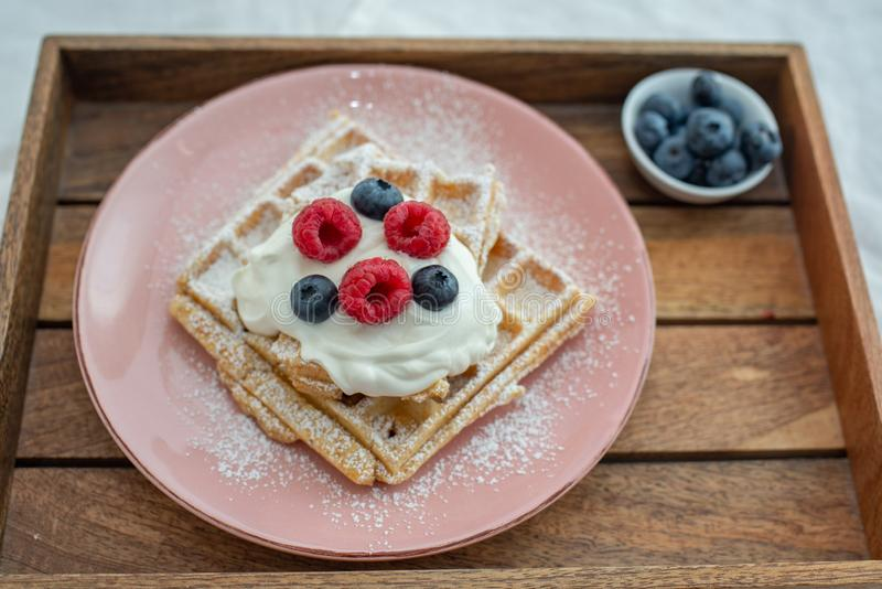 Tasty Belgian waffles with clotted cream and berries on plate royalty free stock image