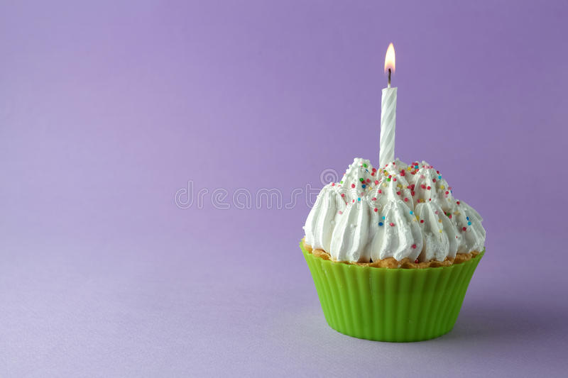 Tasty birthday cupcake with candle, on purple background, with free space stock photography