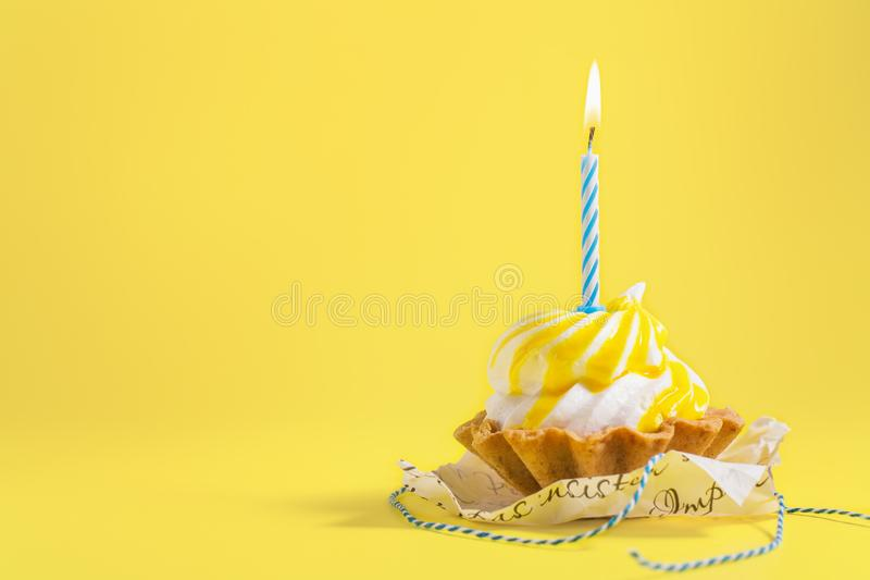 Tasty Birthday cupcake with candle on yellow background with copy space. Delicious muffin on color background. royalty free stock image