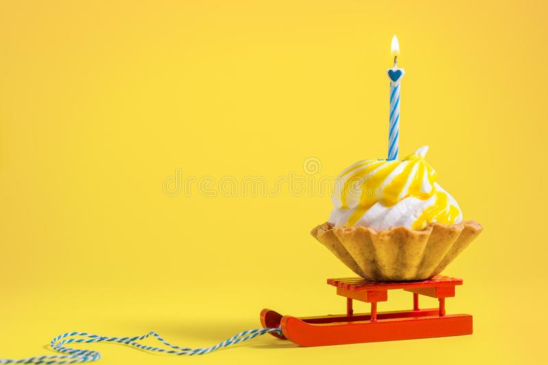 Tasty Birthday cupcake with candle on yellow background with copy space. Delicious muffin on color background. stock image