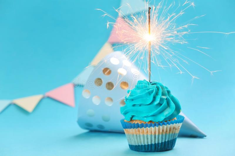 Tasty birthday cupcake with sparkler and party hat on color background stock photo