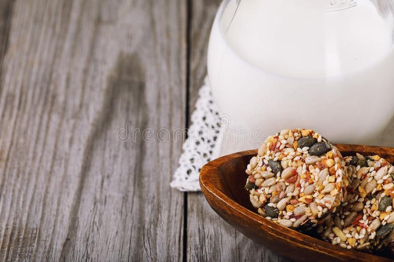 Tasty biscuits from various seeds and dried fruits with milk on a wooden table stock image