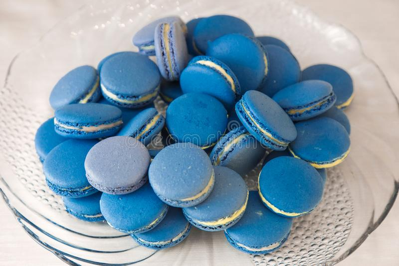 Tasty blue macarons on a plate close up. Color of the year 2020 classic blue stock images