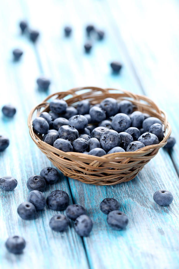 Tasty blueberries. In basket on a blue wooden table stock photo