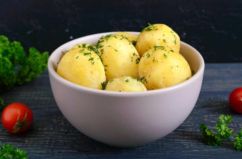 Tasty boiled young potatoes with butter and dill in a bowl on a dark background royalty free stock photo