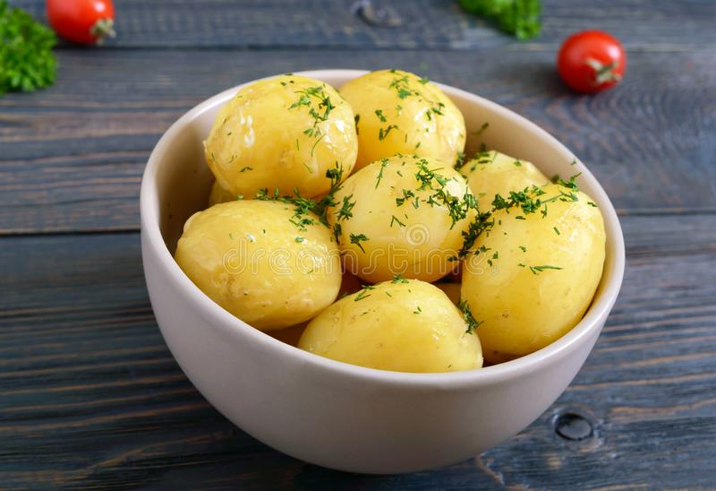 Tasty boiled young potatoes with butter and dill in a bowl on a dark background royalty free stock images