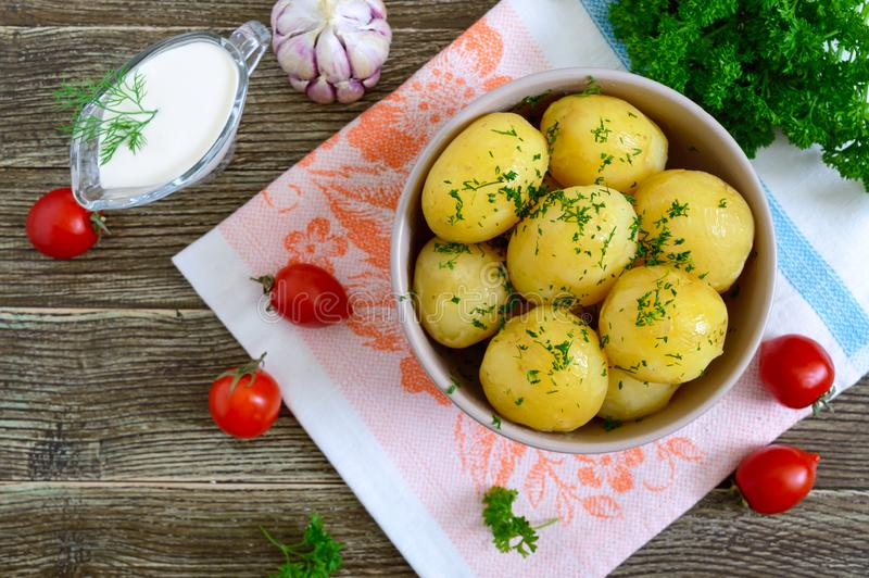Tasty boiled young potatoes with butter and dill in a bowl on a wooden table. Top view, flat lay stock images
