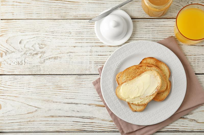 Tasty bread with butter served for on white wooden table, top view. Space for text. Tasty bread with butter served for breakfast on white wooden table, top view stock photography