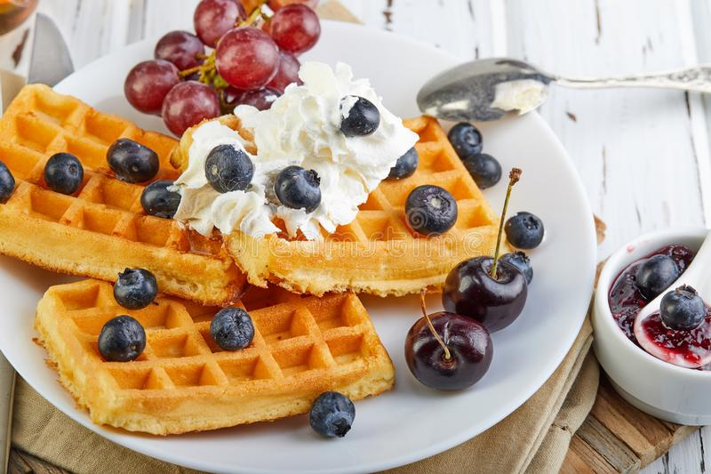 Tasty breakfast. Belgian waffles with whipped cream blueberries and jam on a wooden white stock photo