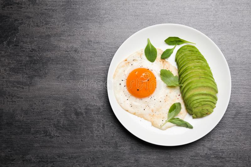 Tasty breakfast with fried egg and avocado on grey table. Space for text. Tasty breakfast with fried egg and avocado on grey table, top view. Space for text stock image
