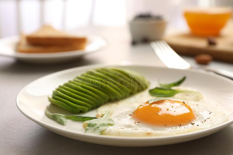 Tasty breakfast with fried egg and avocado on table. Closeup stock image