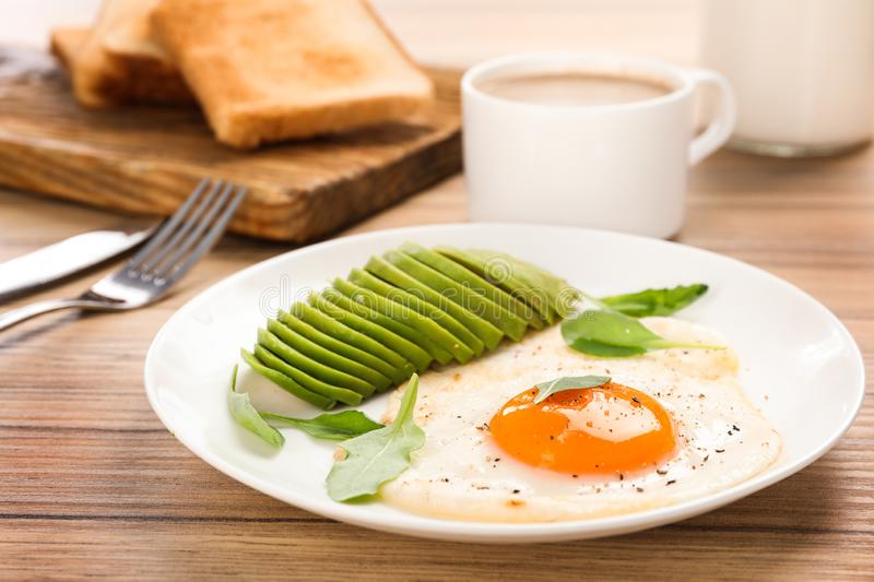 Tasty breakfast with fried egg and avocado on table, closeup. Tasty breakfast with fried egg and avocado on wooden table, closeup stock images