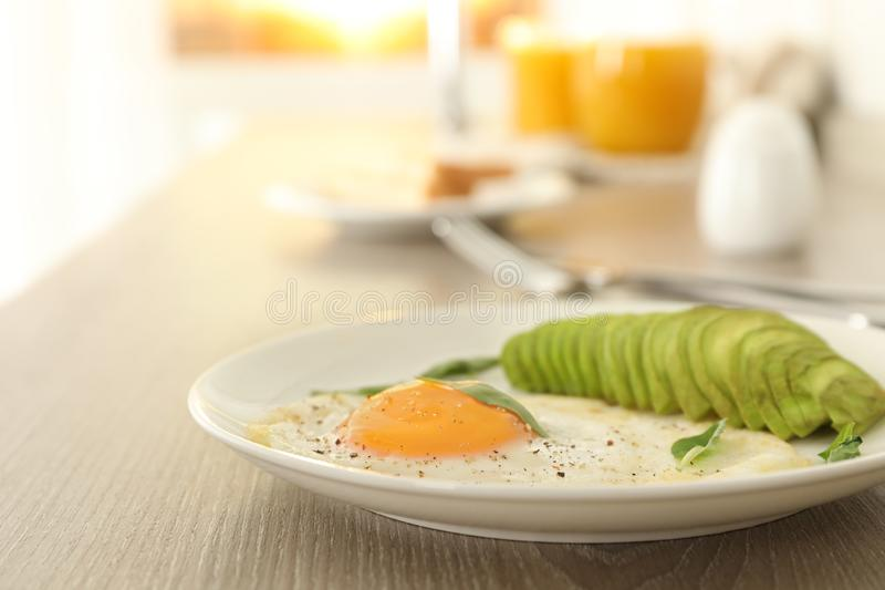 Tasty breakfast with fried egg and avocado on wooden table. Closeup stock image