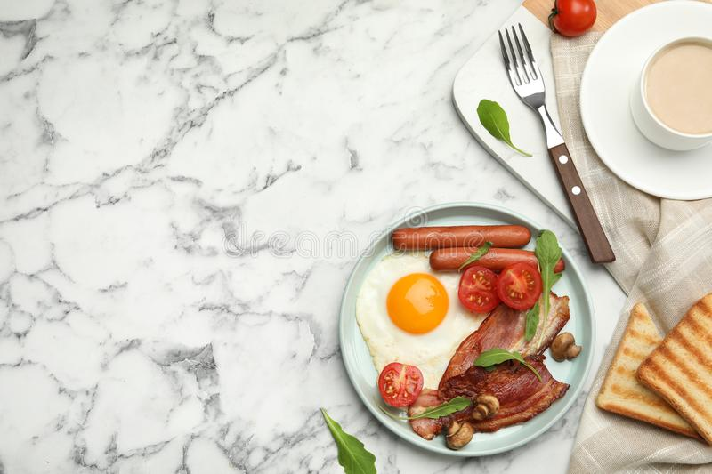 Tasty breakfast with fried egg served on white marble table, flat lay. Space for text royalty free stock photo