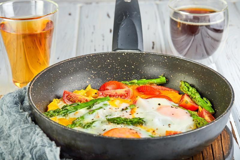 Tasty breakfast. Fried eggs in a pan with coffee royalty free stock photography