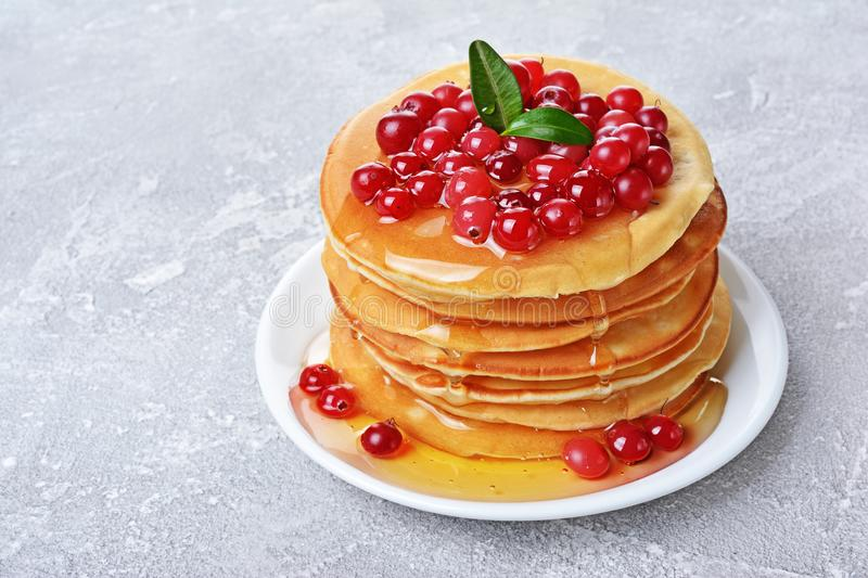 Tasty breakfast. Homemade pancakes with fresh cranberry, honey or maple syrup royalty free stock photography