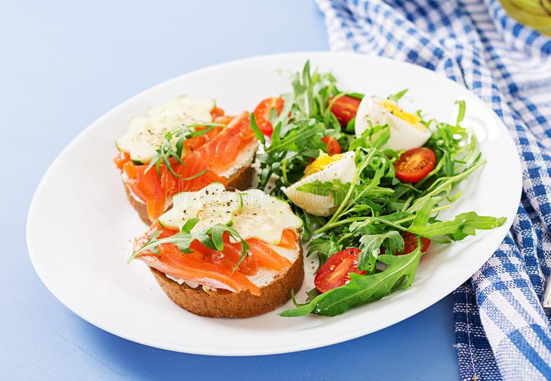 Open sandwiches with salmon, cream cheese and rye bread. Tasty breakfast. Open sandwiches with salmon, cream cheese and rye bread in a white plate and salad with royalty free stock image