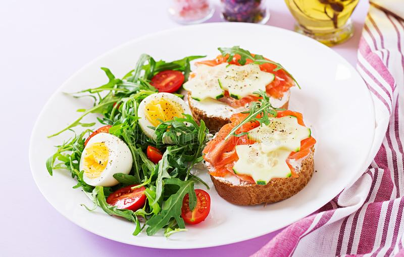 Open sandwiches with salmon, cream cheese and rye bread. Tasty breakfast. Open sandwiches with salmon, cream cheese and rye bread in a white plate and salad with royalty free stock photo
