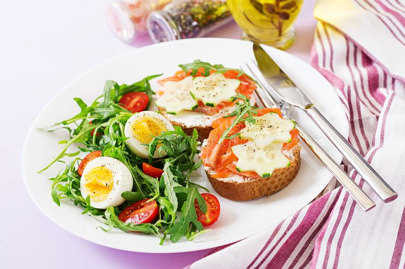 Open sandwiches with salmon, cream cheese and rye bread. Tasty breakfast. Open sandwiches with salmon, cream cheese and rye bread in a white plate and salad with stock images