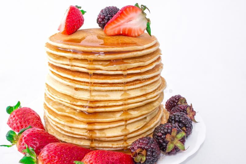 Tasty breakfast. Pancakes with fruit, strawberries and blackberries mora pour syrup honey on a white background. Close-up. stock photography