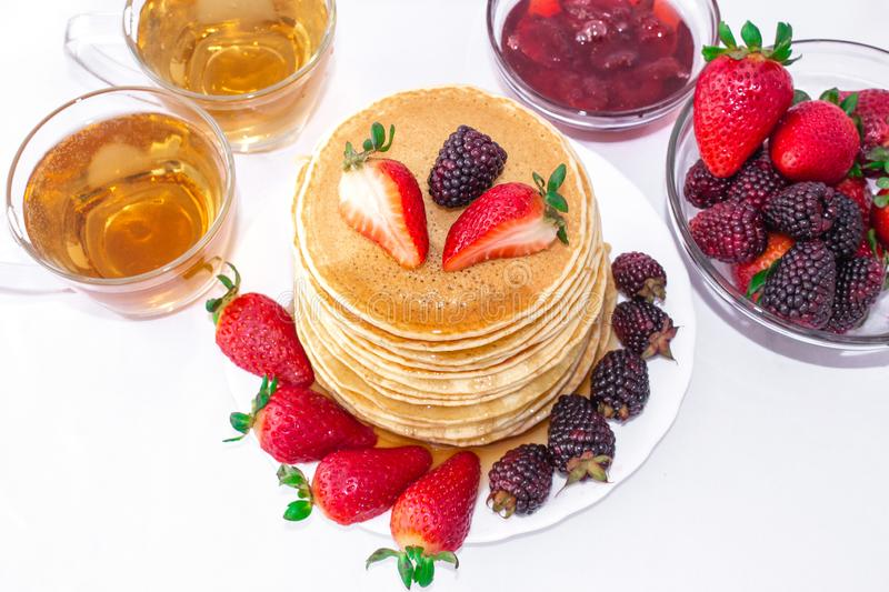Tasty breakfast. Pancakes with fruit, strawberries and blackberries mora pour syrup honey on a white background. Close-up. royalty free stock photo
