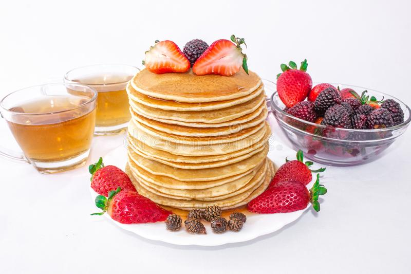 Tasty breakfast. Pancakes with fruit, strawberries and blackberries mora pour syrup honey on a white background. Two cups of tea. royalty free stock image