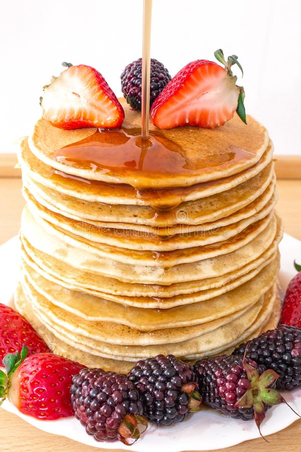 Tasty breakfast. Pancakes with fruit, strawberries and blackberries mora, poured syrup honey on a wooden tray. royalty free stock image