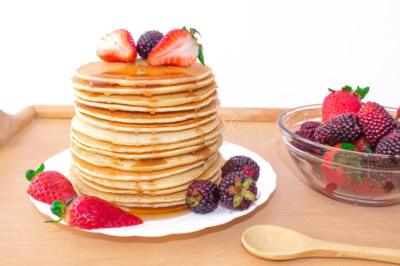 Tasty breakfast. Pancakes with fruit, strawberries and blackberries mora, poured syrup honey on a wooden tray. royalty free stock photo