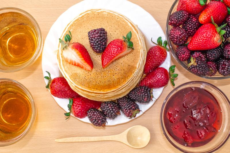 Tasty breakfast. Pancakes with fruit, strawberries and blackberries mora, poured syrup honey on a wooden tray. royalty free stock images