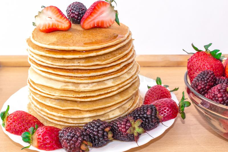 Tasty breakfast. Pancakes with fruit, strawberries and blackberries mora, poured syrup honey on a wooden tray. stock photos
