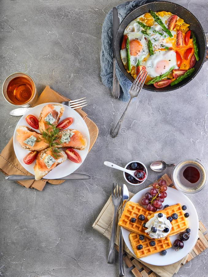 Tasty breakfast. Scrambled eggs in a pan, sandwiches with straw and cheese and Belgian waffles on a wooden white royalty free stock photos