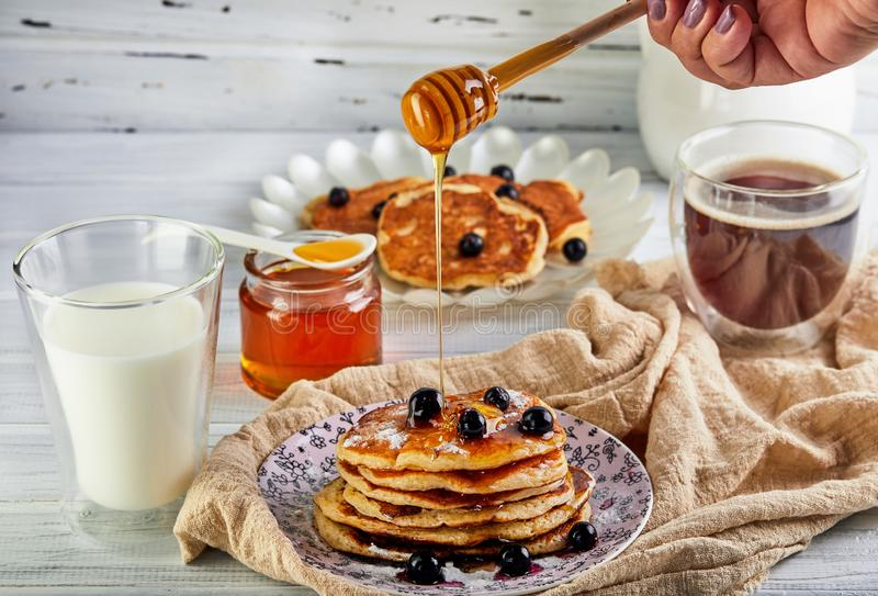 Tasty breakfast. A stack of pancakes with honey syrup a glass of milk, espresso coffee and honey on a wooden white stock photos