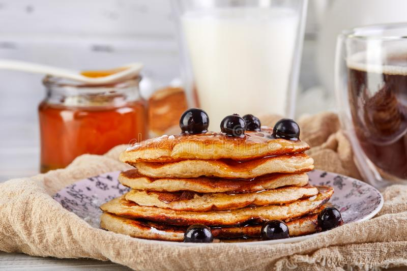 Tasty breakfast. A stack of pancakes with honey syrup a glass of milk, espresso coffee and honey on a wooden white royalty free stock photos
