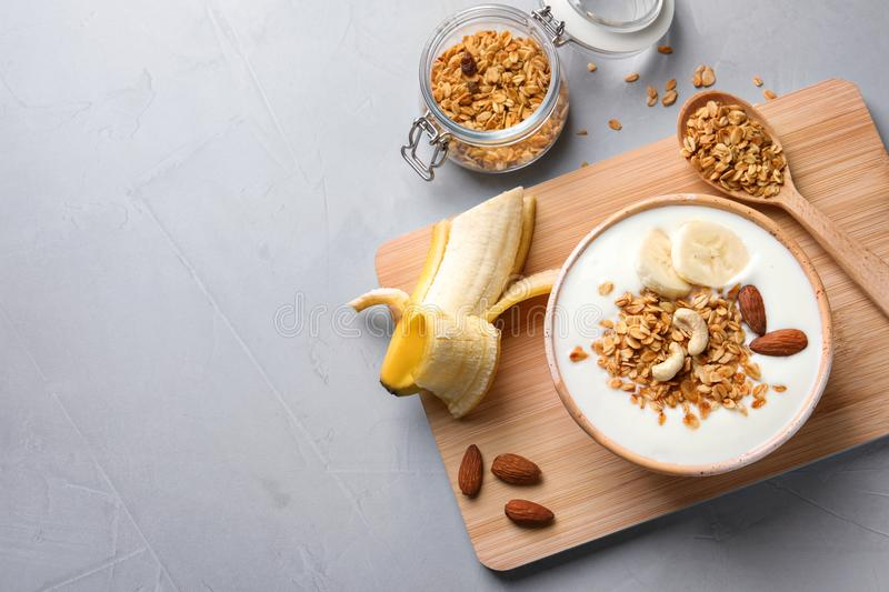 Tasty breakfast with yogurt, banana and granola. On table, top view stock photography