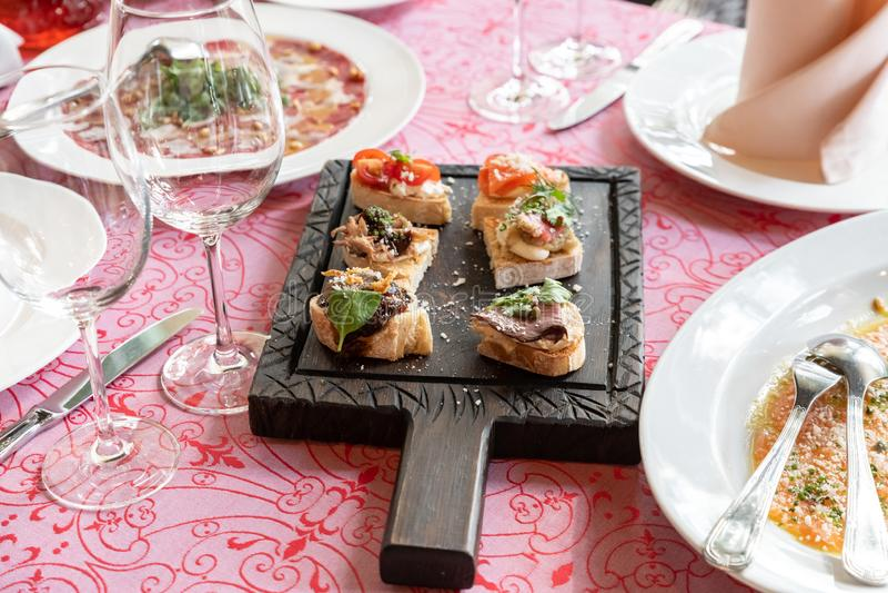 Tasty bruschettas with sun-dried tomatoes on wooden board, closeup stock photo