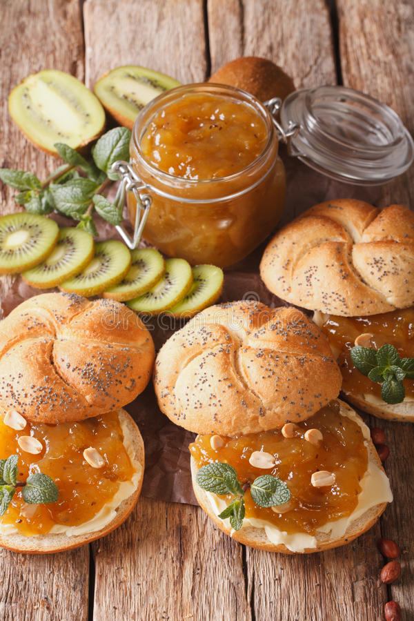 Tasty buns with butter and kiwi marmalade, mint and peanuts close-up. Vertical. Tasty buns with butter and kiwi marmalade, mint and peanuts close-up on the table royalty free stock photography