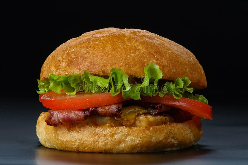 Tasty burger with bacon and tomatoes royalty free stock photo