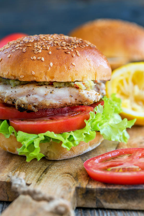 Tasty burger with chicken, tomato and spicy sauce. Burger with chicken, tomato and hot sauce on a wooden table royalty free stock photos