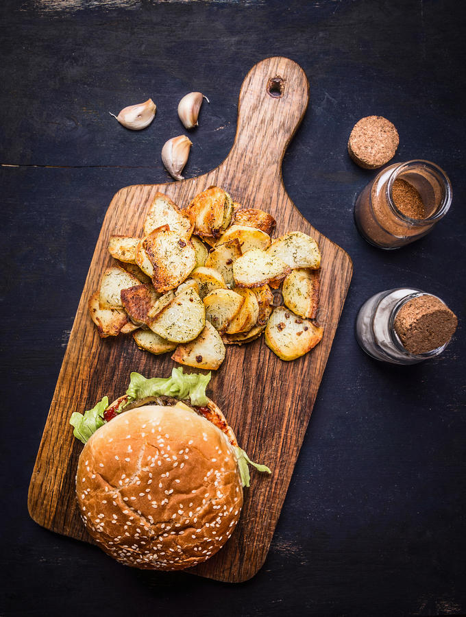 Tasty burger on cutting board with potato wedges with salt and pepper and garlic wooden rustic background top view close up. Tasty burger on cutting board with stock photography