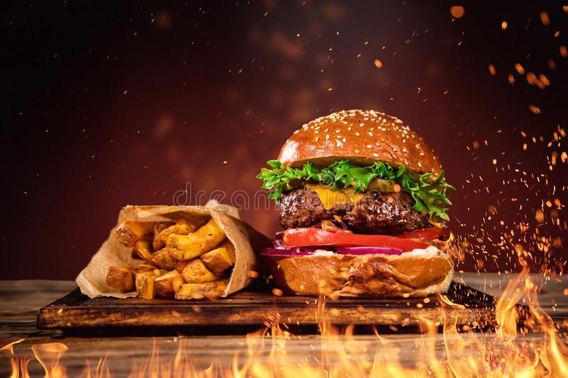 Tasty burger with french fries and fire. royalty free stock image
